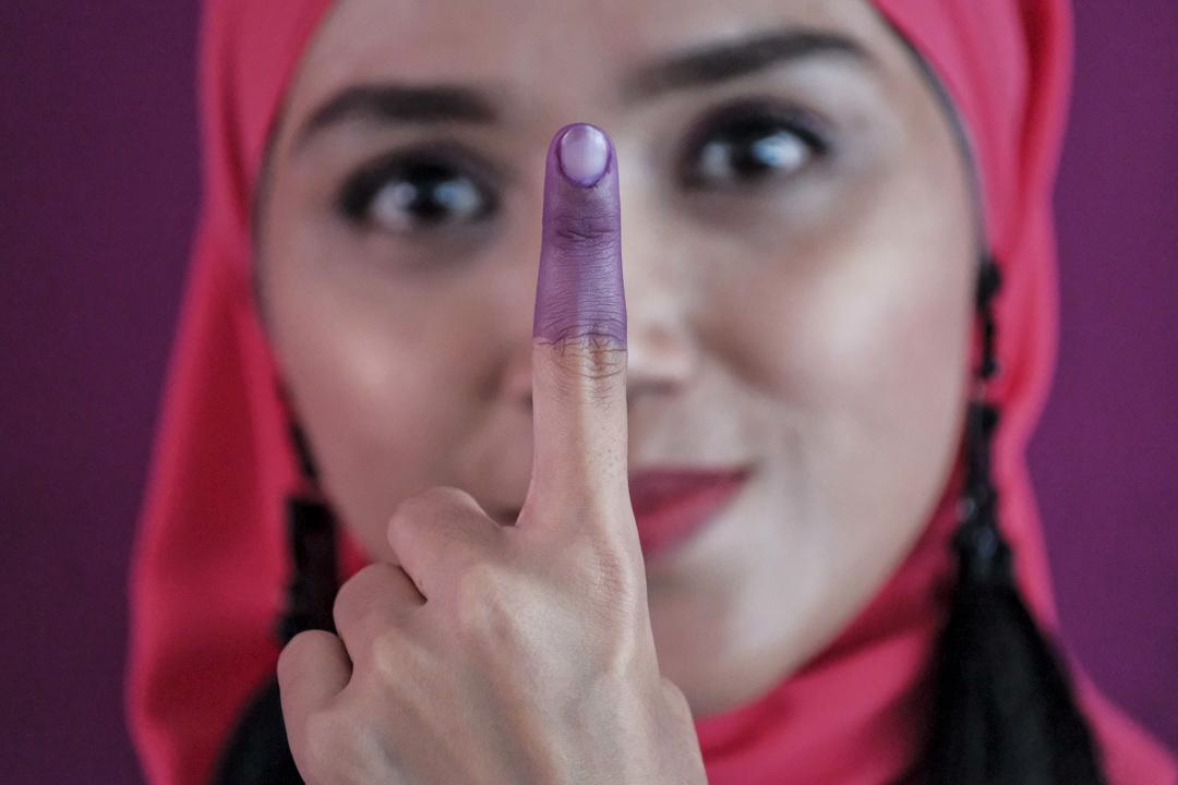 2018年5月9日,馬來西亞大選投票日,選民投票後展示她的「藍手指」。因馬來西亞官方避免選民重複投票,選民的食指會於投票時沾上墨水,開始呈淡紫色,隨時間久了會呈深紫色,會持續大約2天不退色。 攝:Imagine China
