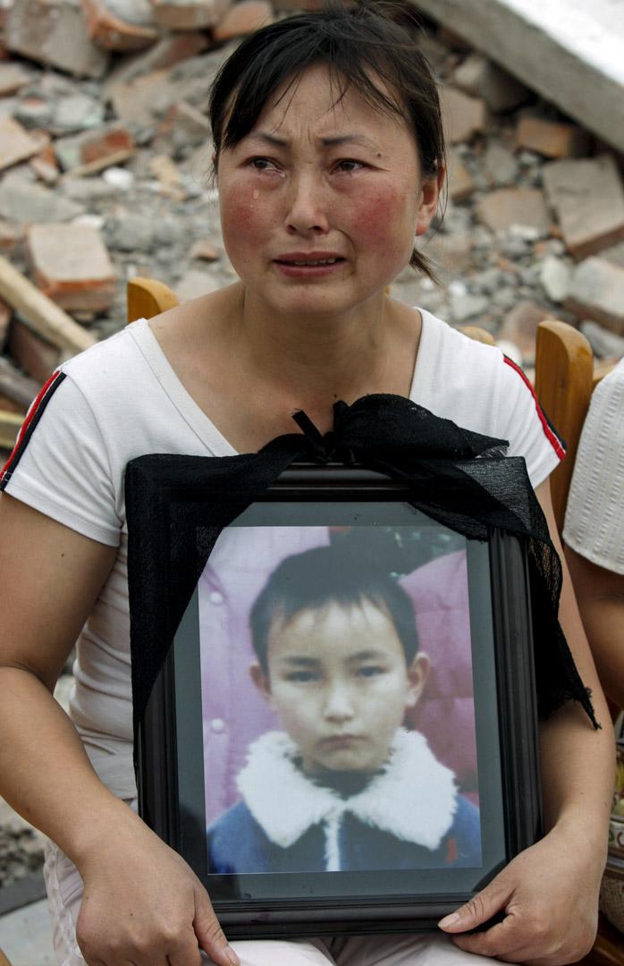 2008年5月22日,四川地震後富新二小的廢墟上,劉孟瑛捧著兒子的遺照。