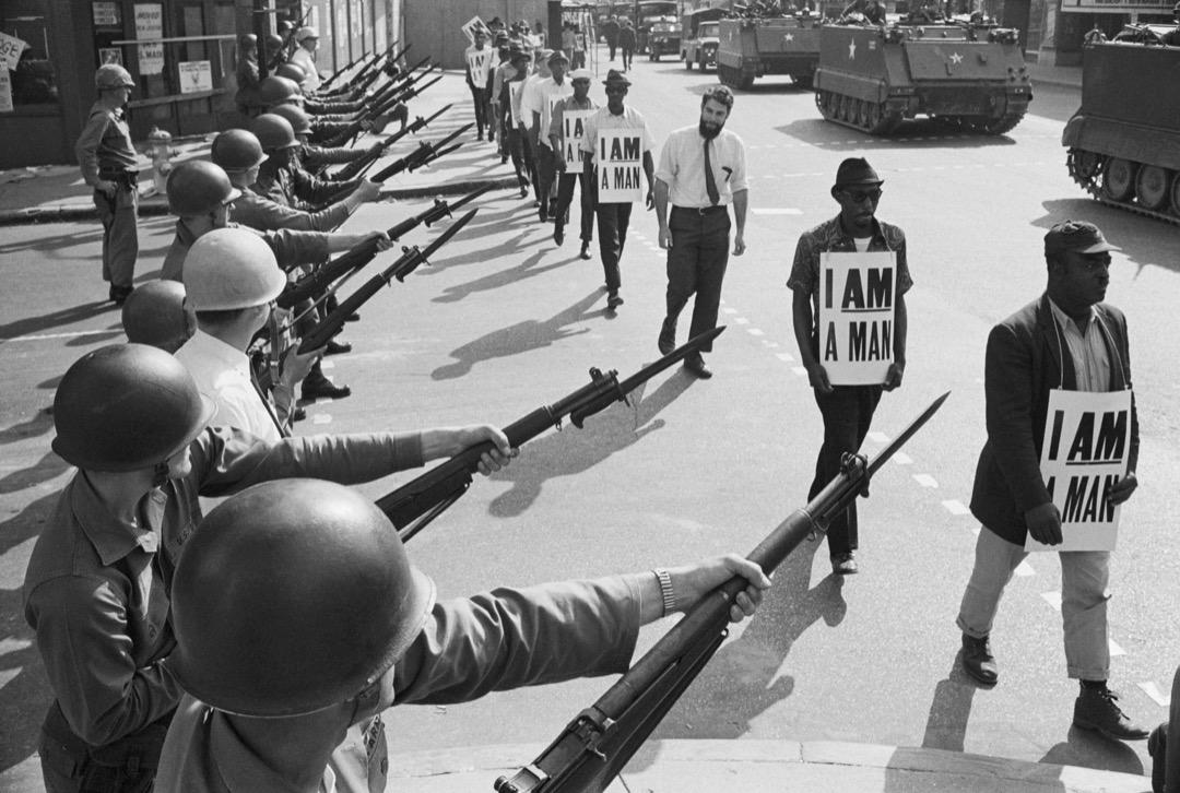 3月29日,美國田納西州孟菲斯市,由非裔美國人民權運動領袖馬丁·路德·金帶領的清潔工罷工運動步入第三週,清潔工人戴上「I AM A MAN」紙牌遊行示威,配備步槍的國民警衛隊在旁戒備。