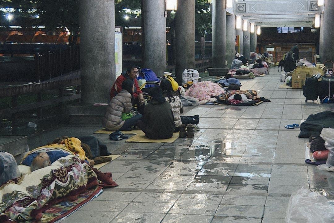 小組成員圍著元瑞坐在紙板上,周圍是還在睡夢中的無家者以及大大小小用塑膠袋或旅行袋裝著的家當,公園檐廊上還滴著水。