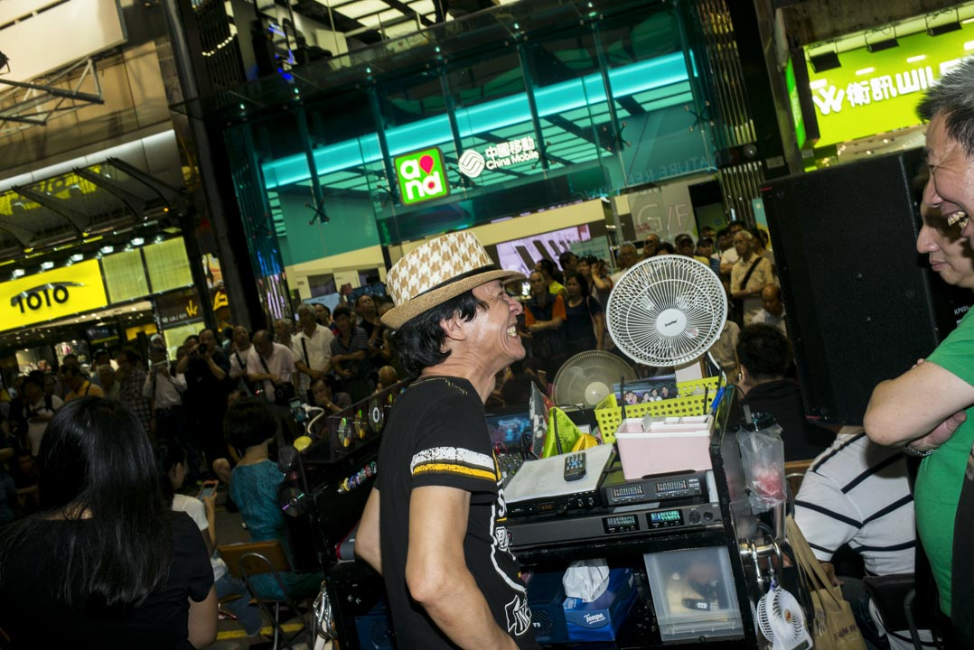 頭戴草帽的「旺角羅文」梁志源,一手一腳組織起來的「旺角羅文歌舞團」,成為菜街最大的卡拉OK歌舞團。