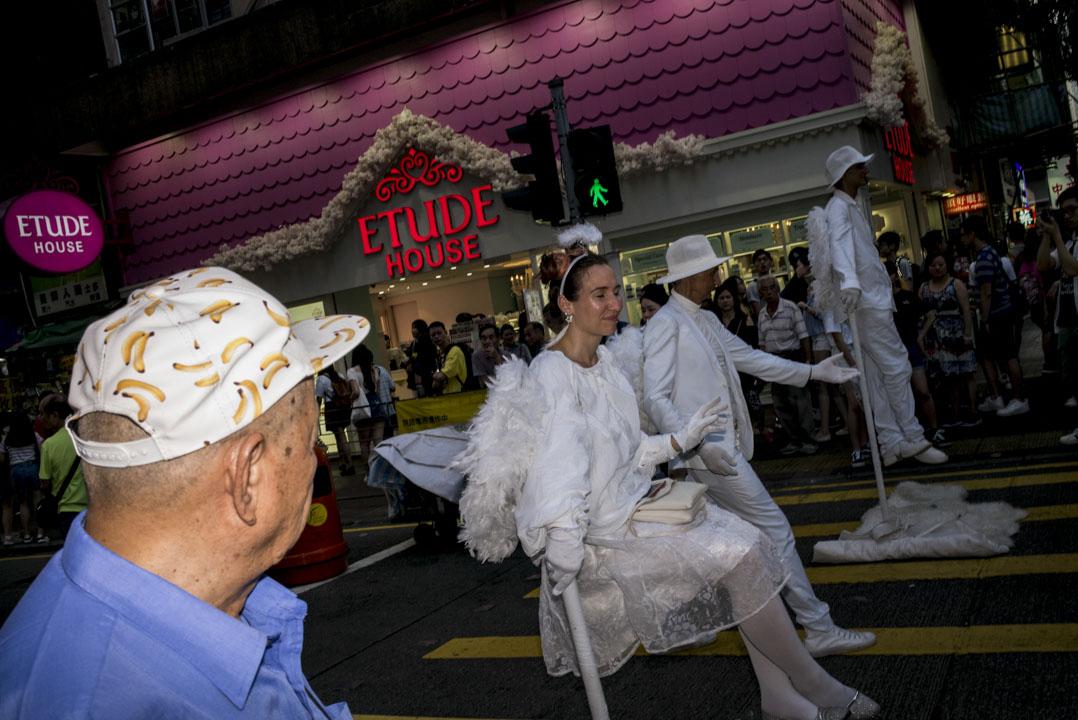 三位穿著白色衣飾的表演者。