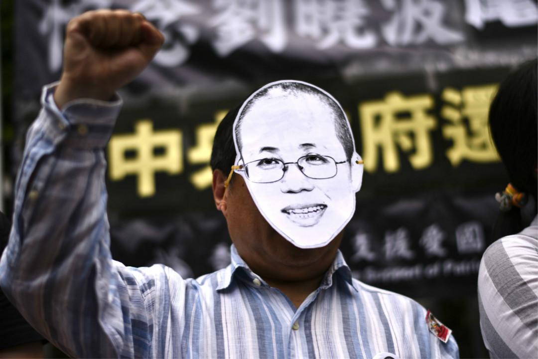 2017年8月30日,香港前立法會議員何俊仁帶上劉霞肖像面具,呼籲中國當局還劉霞自由。 攝:Anthony Wallace/Getty Images