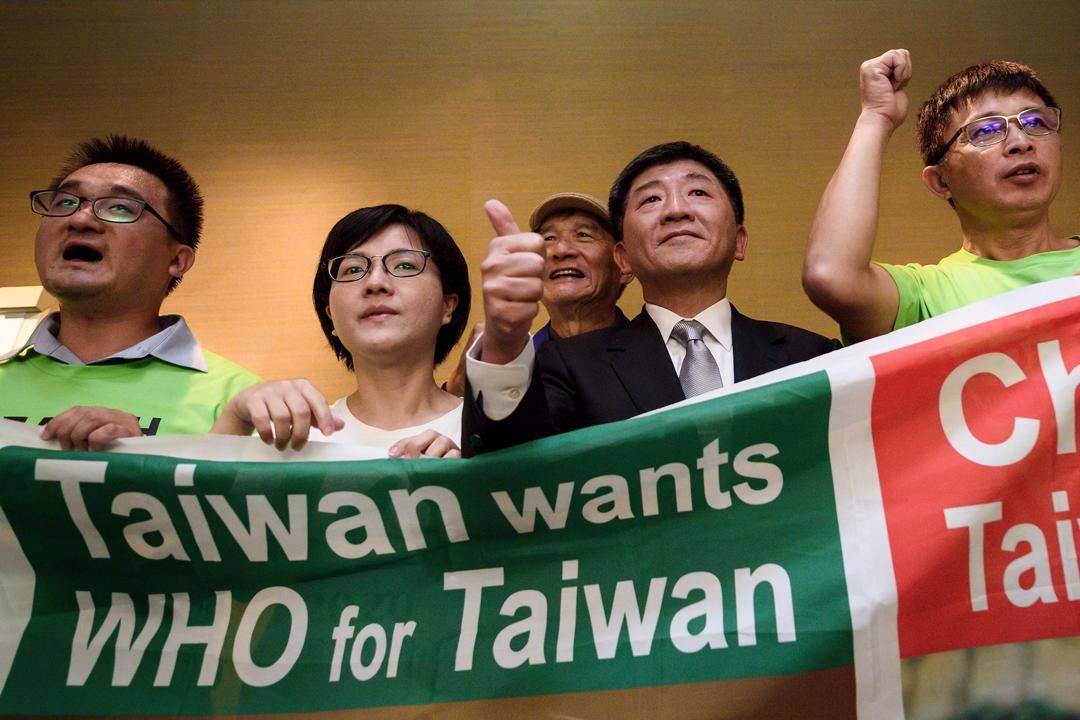 當地週一(21日),台灣衛生福利部長陳時中在瑞士日內瓦出席記者會後,與數名抗議世衛大會拒台灣於門外的示威者一同舉起橫額合照。 攝:Fabrice Coffrini / AFP / Getty Images