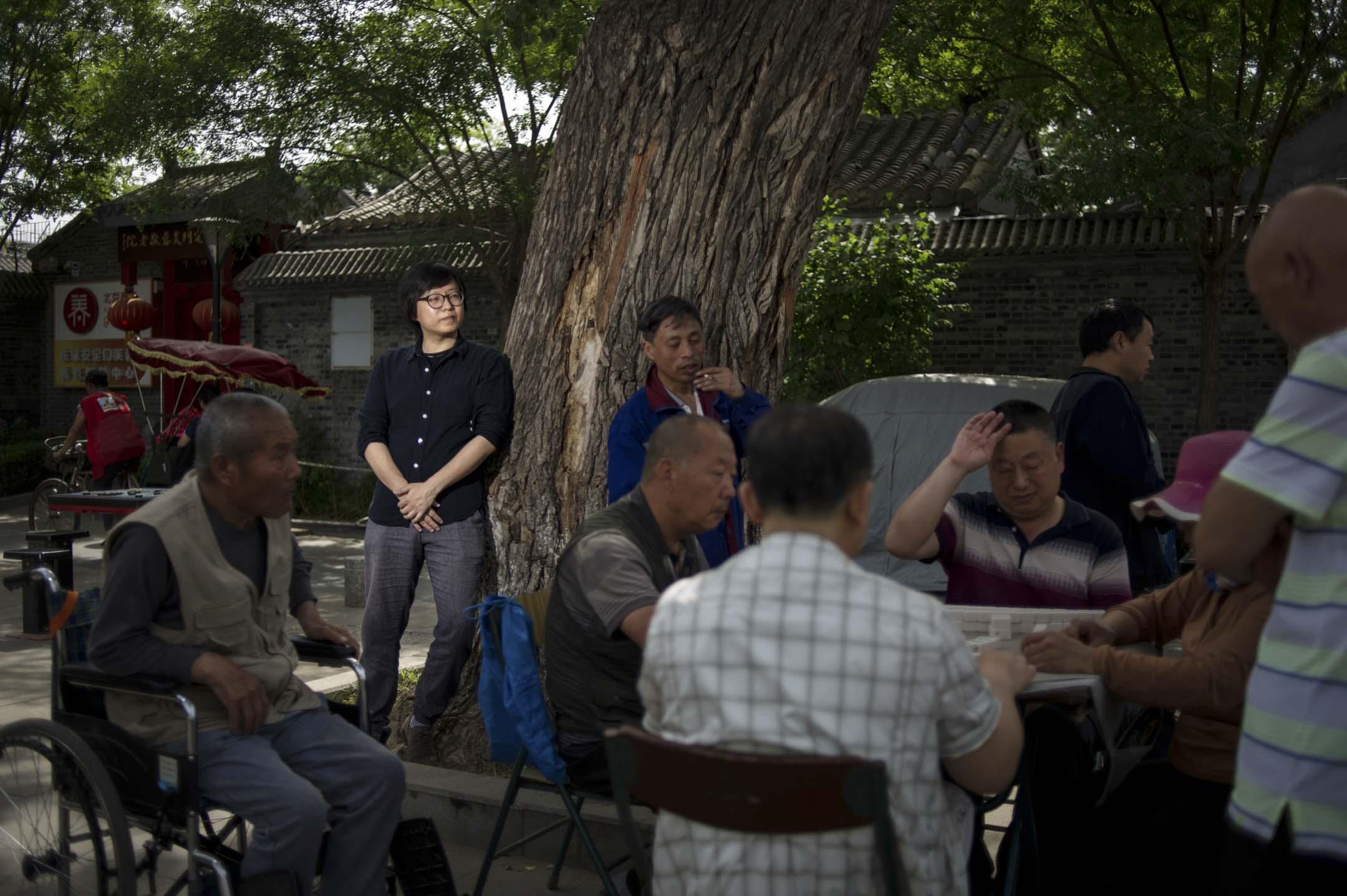 朱起鵬站在胡同當中,看着穿睡衣和拖鞋的中年女人牽着柯基犬走出家門,在路邊閒坐,上了年紀的大爺大媽聚在樹蔭下,搬出自家的桌椅板凳,打麻將、喝茶。「他們沒有把胡同當做公共領域,而是當成起居空間。」 攝:Gabriel/端傳媒