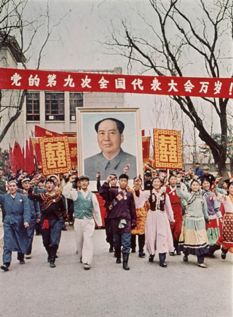 文革期間,中國有人手持毛澤東巨型肖像在街上遊行。