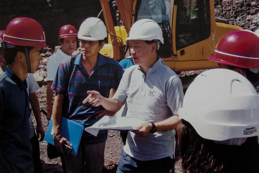唐錫波在南江縣朝陽中學建築工地上視察。