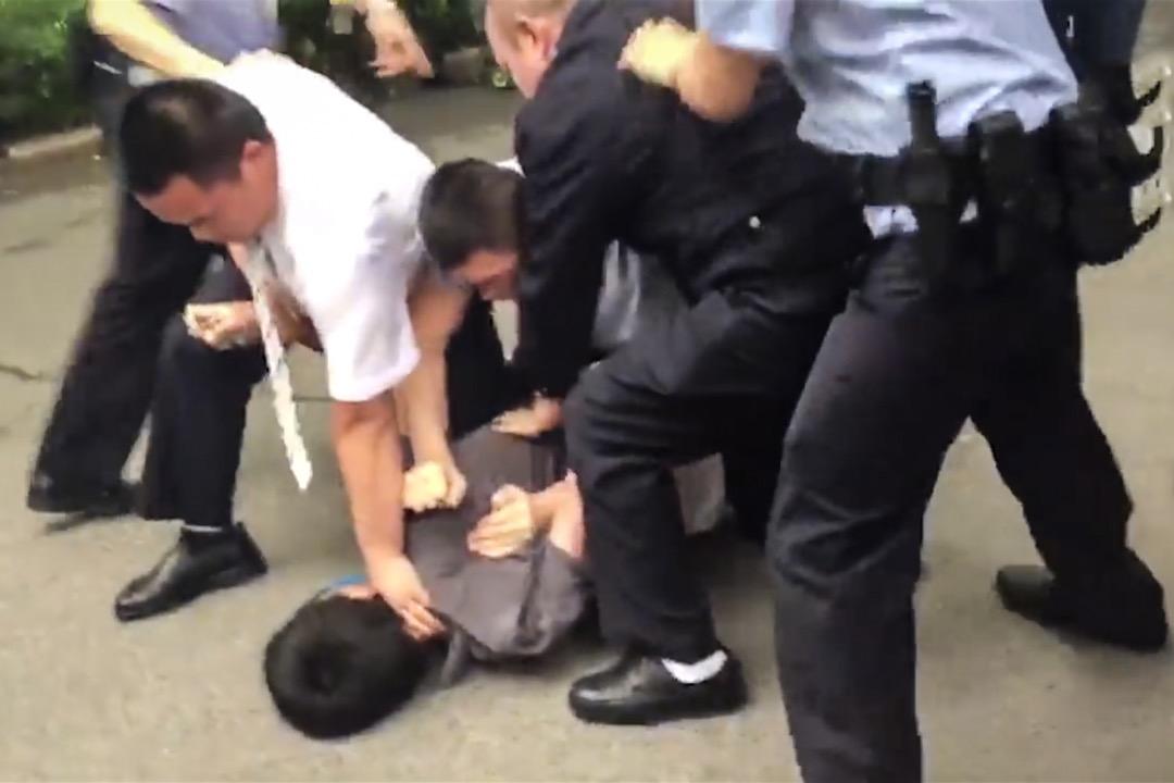 香港 now 新聞台駐北京攝影師徐駿銘今早採訪時遭遇警員以武力阻撓,期間被多名警員壓在地上致額頭受傷流血,又被鎖上手扣、強行押上警車。 圖:新聞片段截圖