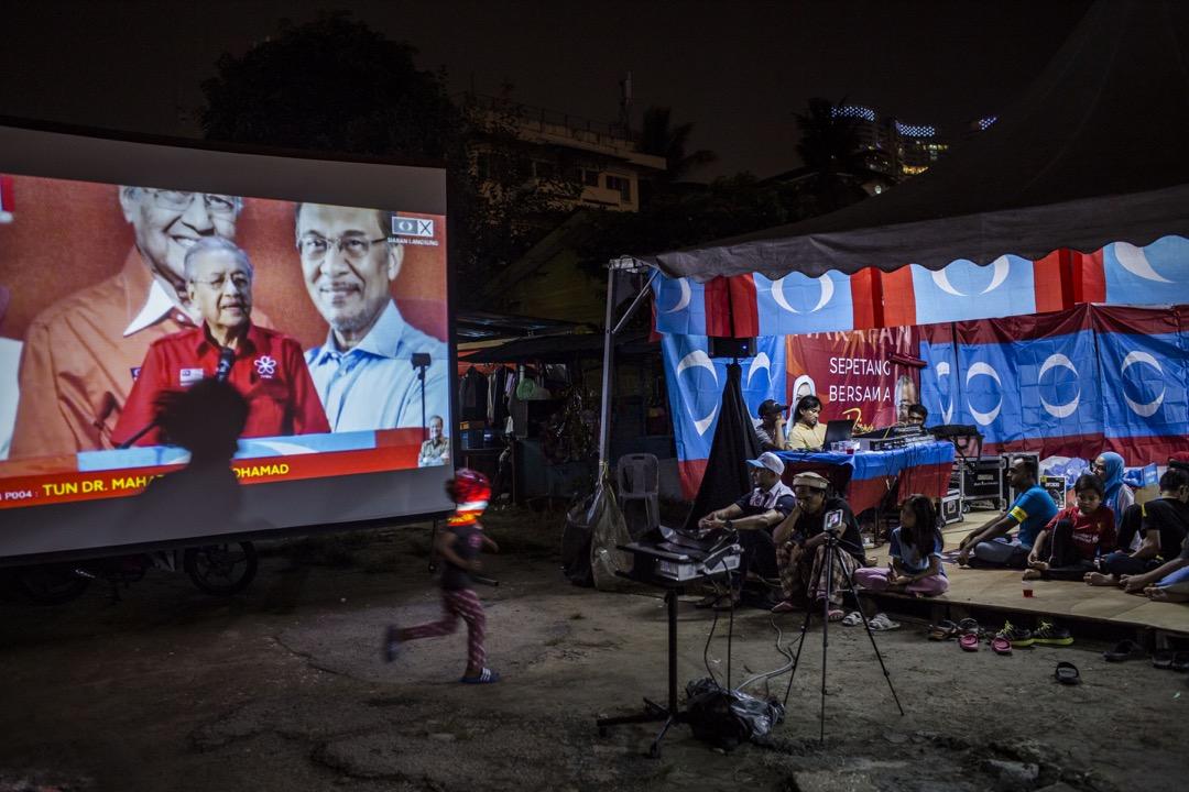 2018年5月8日,馬來西亞大選前夕,希望聯盟支持者透過投影機看希望聯盟首相候選人馬哈蒂爾發表講話。 攝:Ulet Ifansasti/Getty Images