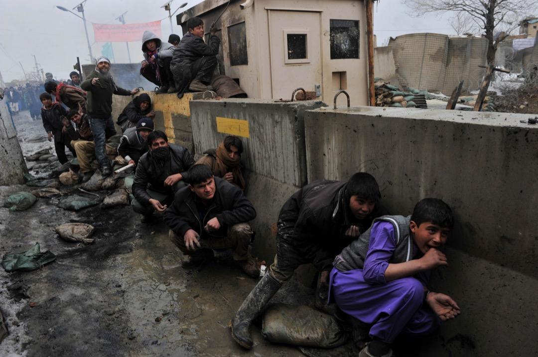 2012年2月21日,美軍在阿富汗東部巴格拉姆美軍基地以橡膠彈驅逐示威民眾,一群阿富汗少年伏在圍牆後躲避。示威者為抗議美軍焚燒和褻瀆《可蘭經》而向美軍基地投擲石頭和汽油彈。
