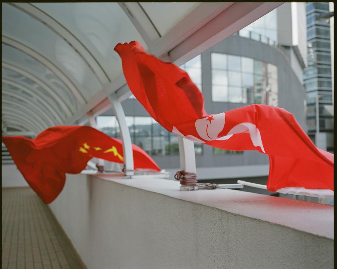 香港一條天橋上,有中國的五星紅旗及香港特區區旗隨風飄揚。  攝:林振東/端傳媒