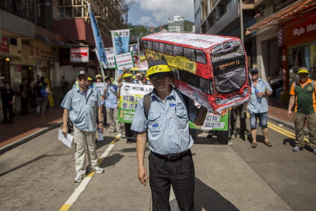 新巴職工會的李先生是一名巴士司機,手捧自製的巴士道具參與五一勞動節遊行。他表示希望公司善待員工,減少工時,避免因疲勞駕駛影響乘客的安全。