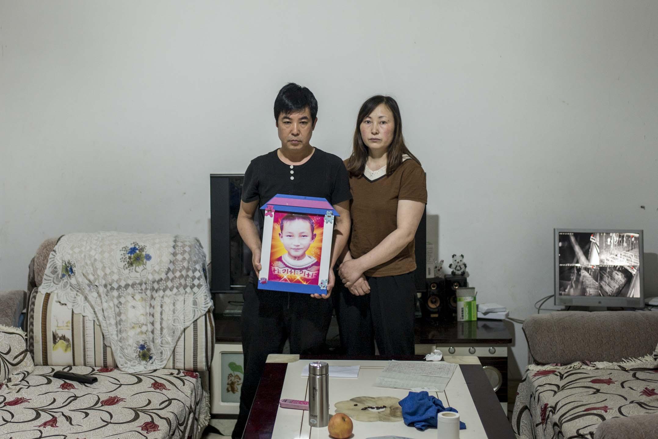 2018年4月,桑軍和劉孟瑛捧著去世兒子的遺照。 攝:林振東/端傳媒