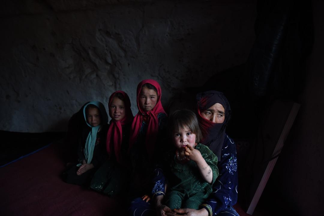 2015年6月19日,喀布爾200公里以西北的巴米揚市,一名哈扎拉女人和她的孩子在她們的洞穴裡坐著。巴米揚谷的數百個人造洞穴裡住進了不少貧困的無家者。