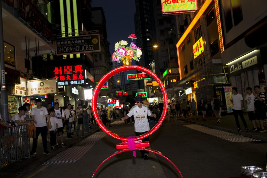 旺角菜街的賣藝江湖是一條魔幻隧道,不少街頭表演者以奇趣賣藝吸引觀眾。 攝:林振東/端傳媒
