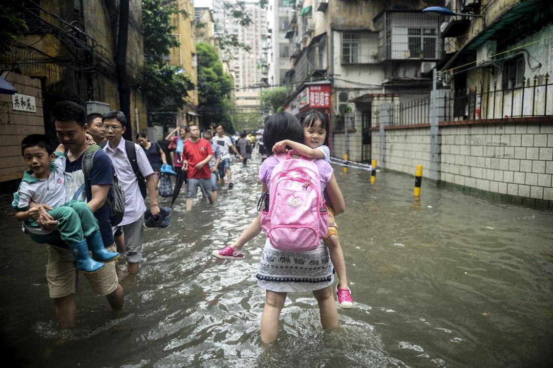 2018年6月8日,中國廣東地區日前遭颱風艾雲尼及暴雨襲擊,雨勢一直不停,廣州不少路皆被水浸,一位家長抱著小朋友涉水而行。 攝:Imagine China