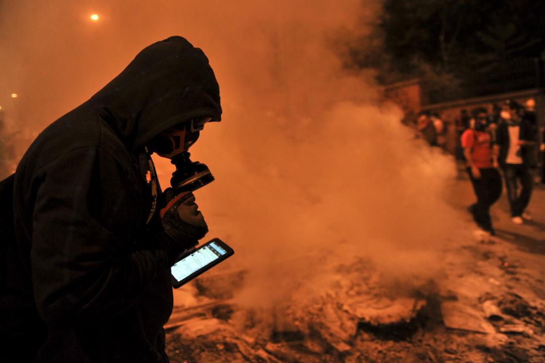 社交網絡和互聯網的影響愈來愈大。一些規模小的團體的動員力也漸漸提高,小事件引發大規模的社會運動的可能性不斷增加。圖為2013年土耳其伊斯坦堡發生的示威,一位示威者在現場使用社區網絡。