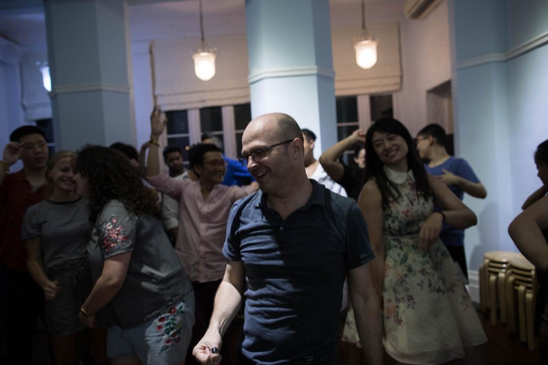 正值六月炎夏,傍晚的天氣侷促而悶熱。在九龍佑寧堂裡一間面積約八百呎的房間裡,合唱團成員們肩貼肩緊密地排成三列,額頭滲著微汗,在歌與歌之間的空隙他們勾肩搭背、互相取笑。