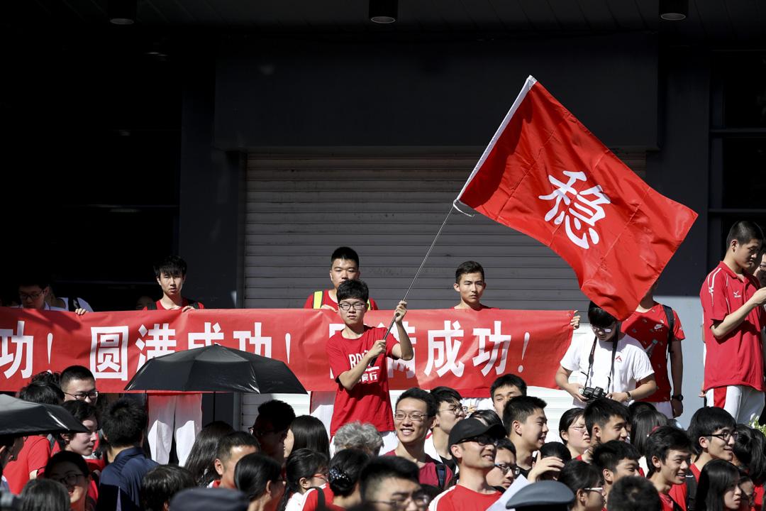 2018年6月7日,北京一個高考試場外,學生揮舞「穩」字標語為高考生打氣。 攝:Imagine China