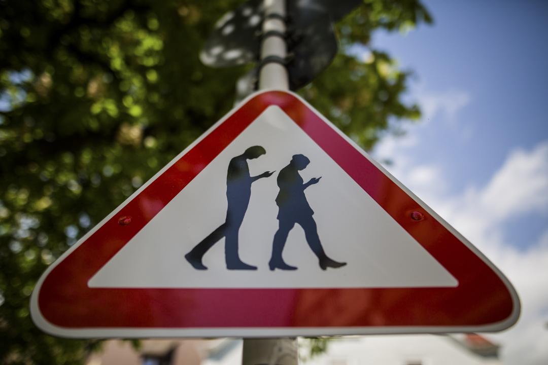 德國於今年元月正式施行的《網絡執行法》,要求社群平台業者須在一定時限內審查與刪除違法內容。圖為2018年4月25日,德國南部城市羅伊特林根一所學校附近,有一個Smombie(手機殭屍)的路牌,指示途人勿在街上行走中觀看手機。  攝:Christoph Schmidt/AFP/Getty Images