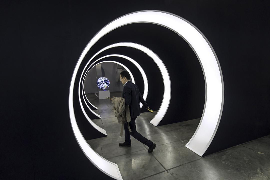 自從2011年上市以來,騰訊所發展的微信(WeChat)已成為中國人民日常生活不可缺少的網絡應用軟體。圖為2018年1月15日,廣州的騰訊微信開放專業會議的入口處,與會者在走過。 攝:Qilai Shen/Bloomberg via Getty Images