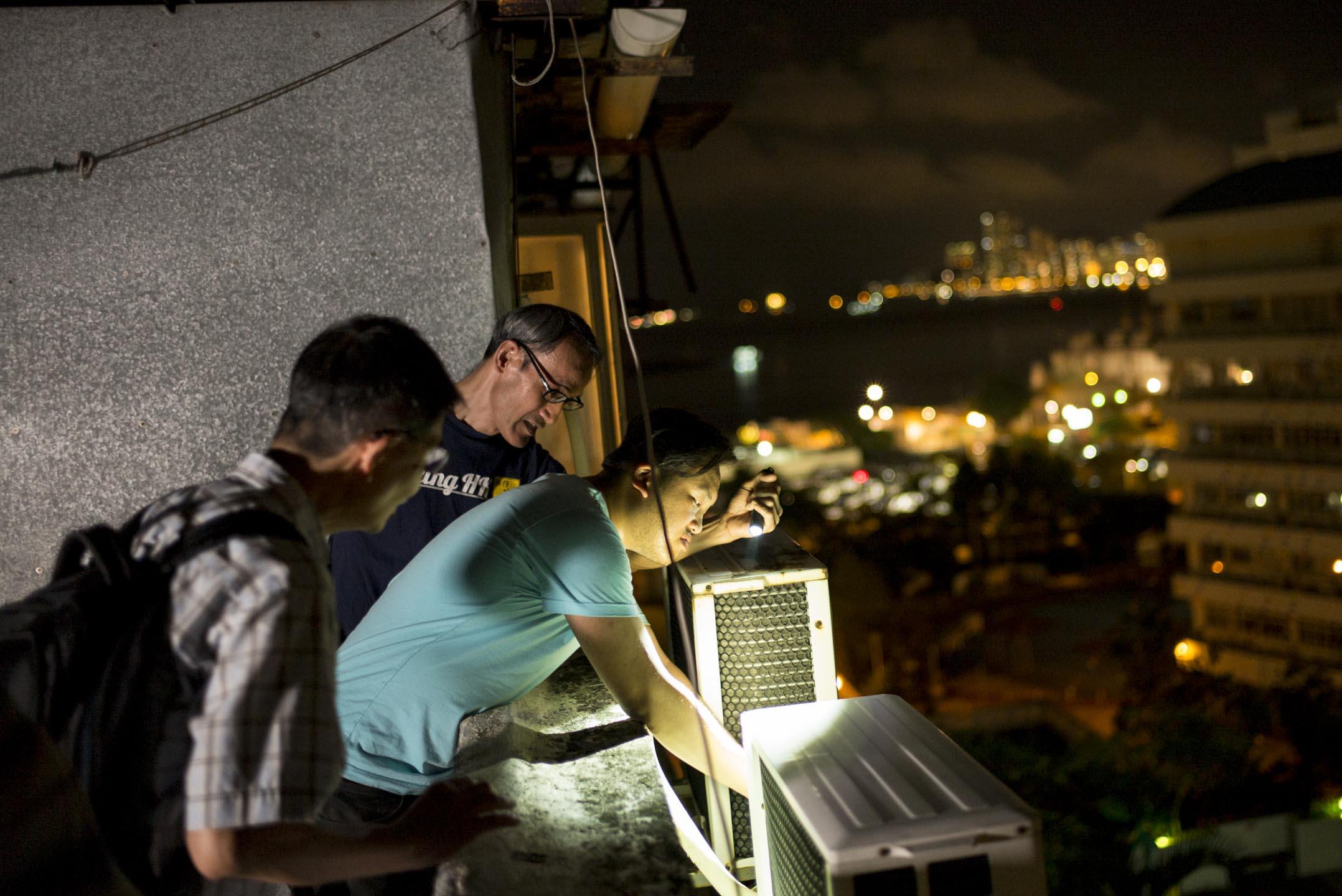 「維修香港」是一支特殊的社區維修隊,每周四,維修隊伍會分隊上樓為街坊義務維修家室,恆常參與者有十、二十多人,往來重訪的不計其數。這天琛師父和文浩到一幢天台屋修理冷氣。 攝:林振東/端傳媒