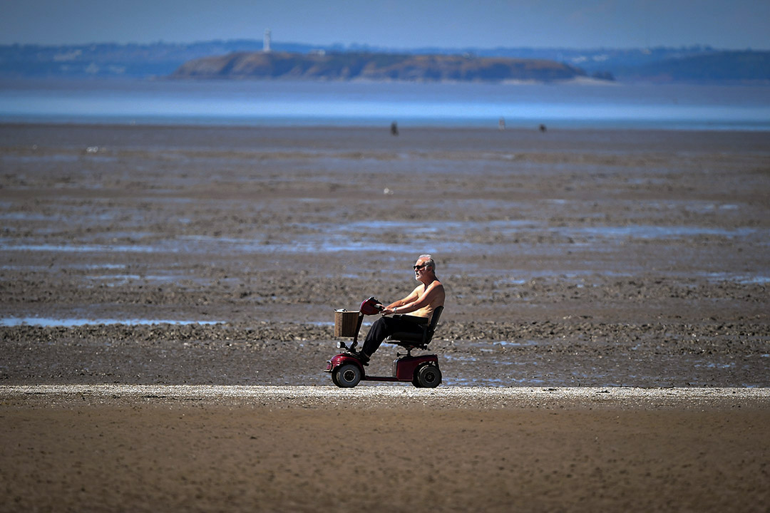2018年7月15日,英國西部城鎮濱海韋斯頓,一名男子坐著電動代步車經過沙灘。