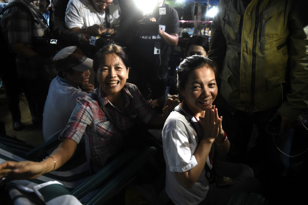 2018年7月2日,泰國北部清萊府湄塞縣探險失聯9天的12名青少年足球運動員和1名教練被找到,且全部活着。被困者家屬在現場附近聽到這個好消息後興奮不已。 攝:Lillian Suwanrumpha/Getty Images