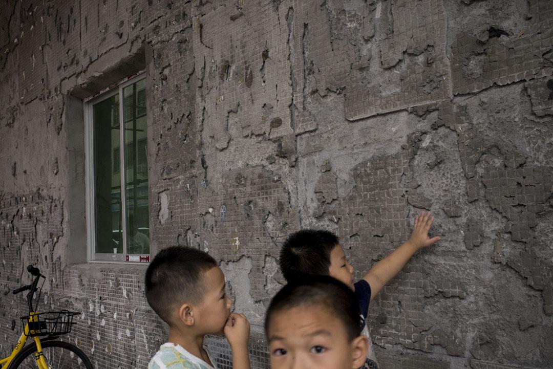 崗頭新圍仔村的小孩在一幢改造中的樓房前。