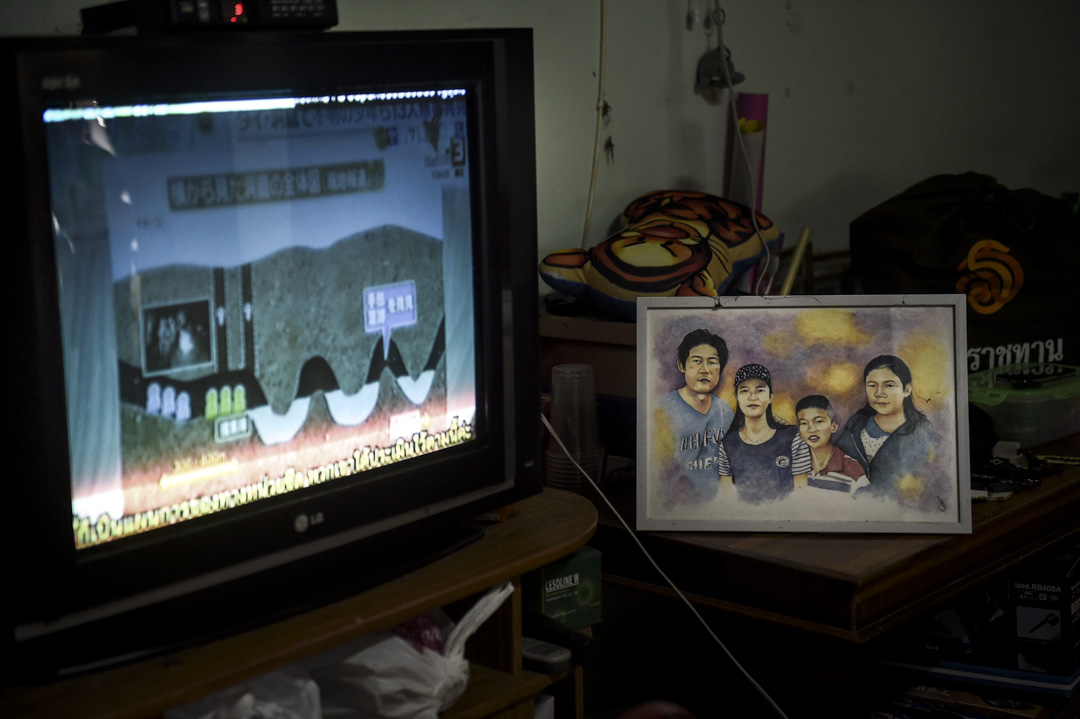 7月4日,電視上正播放著解釋少年足球隊被困洞穴的結構的動畫,旁邊擺放著一幅由其中一名被困少年 Pheeraphat Sompiengjai 所畫的全家福。