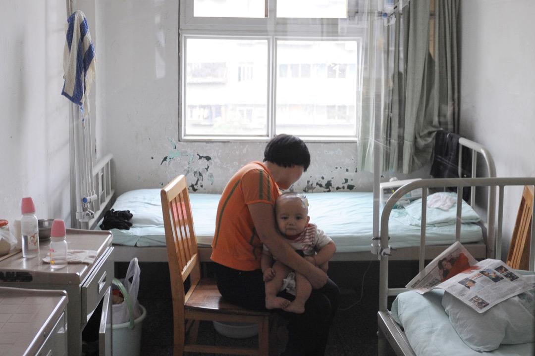 2008年9月22日,成都兒童醫院,一位母親抱著一名因食用受三聚氰胺污染的奶粉而患有腎結石的嬰兒。