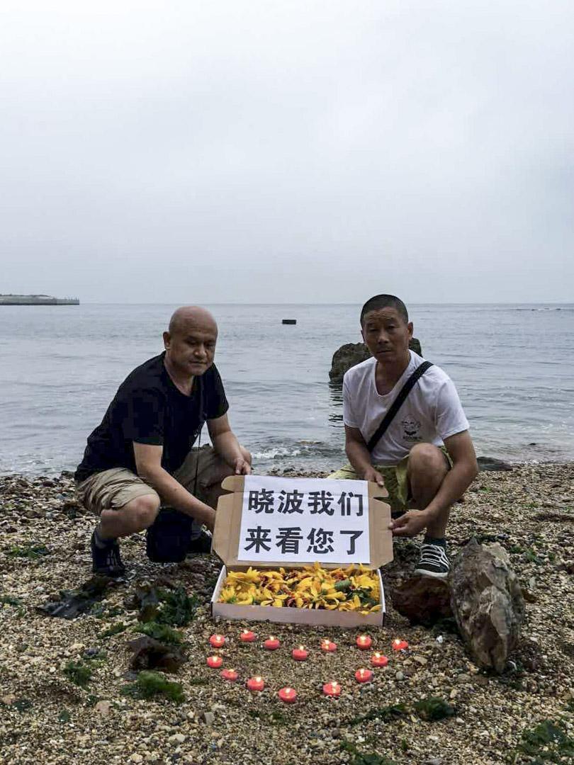 2017年7月18日,遼寧省大連姜建軍、王承剛到當地老虎灘海邊擺放蠟燭、鮮花拜祭劉曉波。