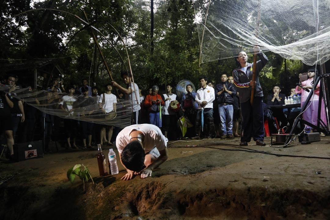 6月26日,家屬在洞穴入口為被困少年祈禱,救援人員在洞穴外支援洞內的搜救隊。