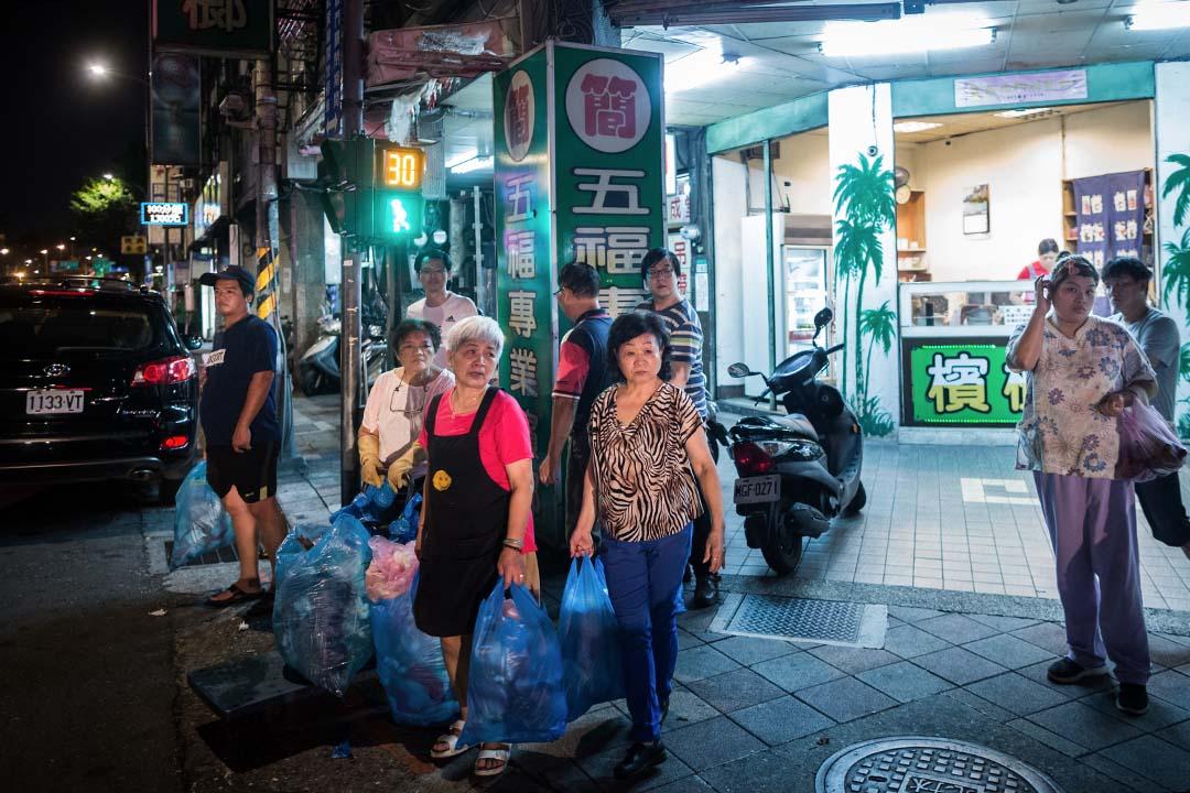 在台灣,垃圾清潔費有兩種收費方式:都會區如雙北市的隨袋徵收是一種,由垃圾袋大小決定承載垃圾量多寡,也決定了個人製造的垃圾,必須付出相對的代價。圖為台北龍山寺的居民等候垃圾車收垃圾。