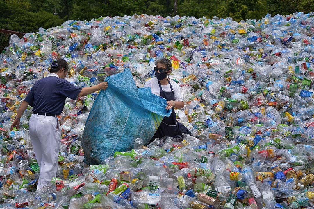 環保署回收制度將塑膠依據原始材質分為一到七號,理論上都是「應回收品項」。圖為志願者在台北回收中心裡作分類工作。