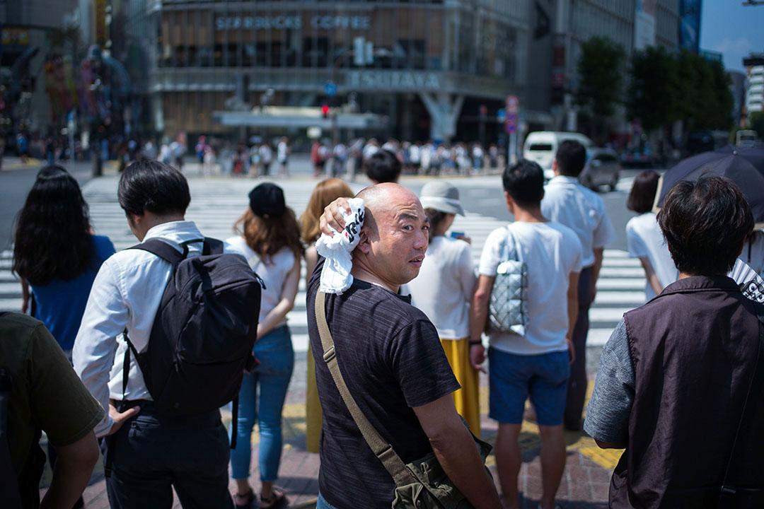 2018年7月24日,日本東京,一名正要過馬路的男子在抹汗。
