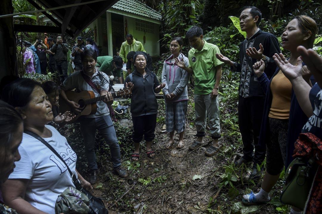 6月27日,被困少年家屬在山洞附近為仍然困在洞穴內的少年足球隊祈禱,有家屬彈起吉他領唱。