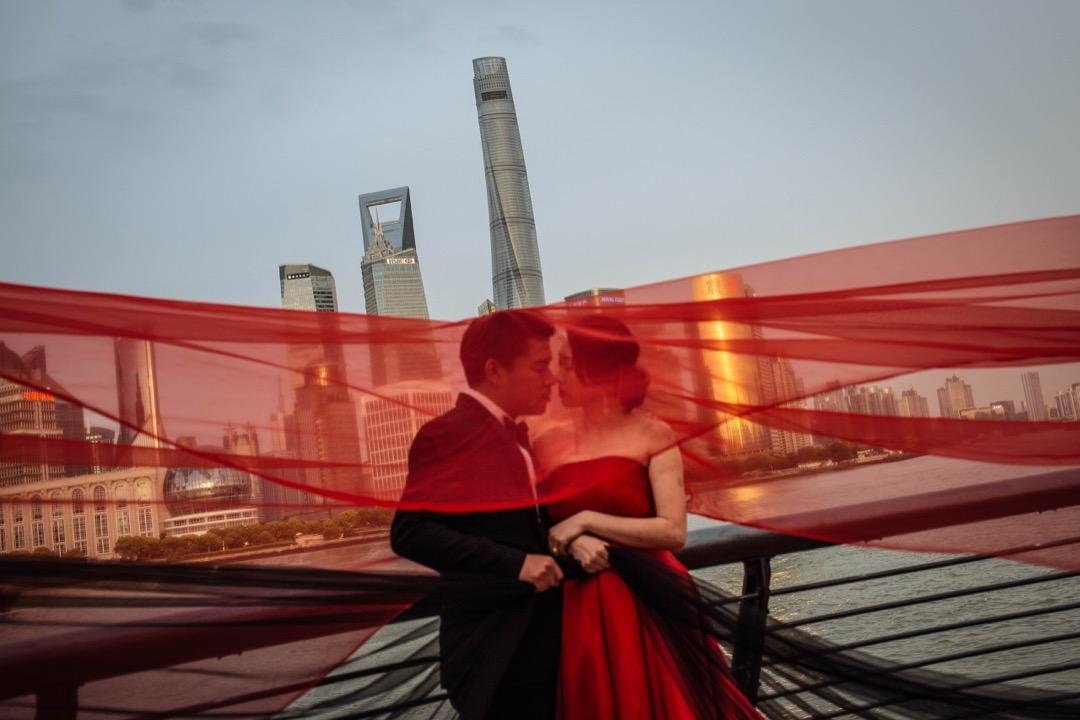 上海中心大廈,樓高632米、共128層,於2016年完工,是目前中國第一高樓,也是世界第二高摩天大樓,僅次於杜拜哈里法塔。圖為一對新人在位於浦東的大樓對岸拍攝婚紗照。