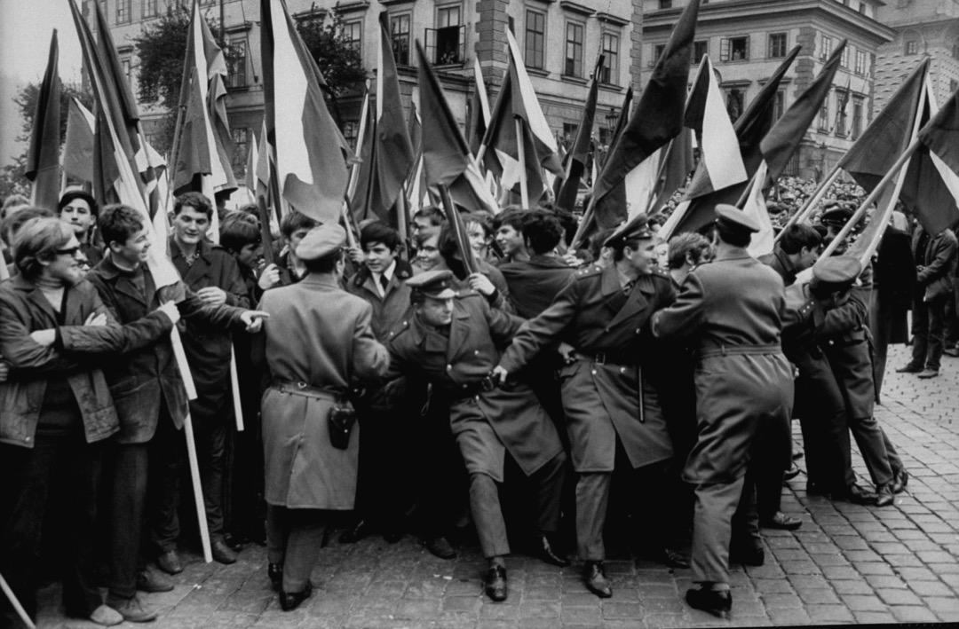 杜布切克最終還是選擇站在民眾的對立面上,呼籲民眾不要抵抗蘇聯軍隊。接下來的幾個月中,杜布切克從捷共開明派領袖一躍變成蘇聯的傀儡。圖為士兵試圖阻止持捷克旗的學生示威。