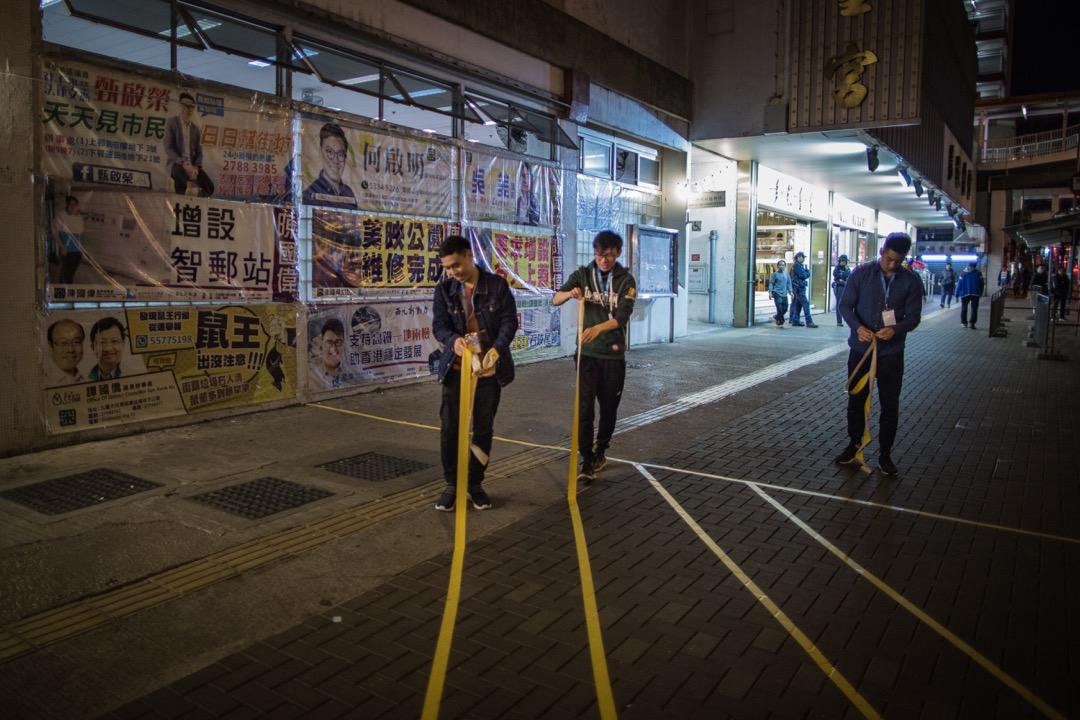 香港選舉管理委員會日前公布2019年區議會選舉選區分界後,引起不少受影響的非建制區議員反對,指政府透過重劃選區分割票源。圖為2018年九龍西立法會補選,石硤尾票站關門後,工作人員在清理現場。 攝:陳焯輝/端傳媒