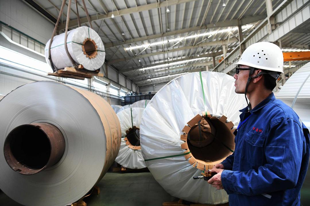 美國和中國7月6日正式對價值340億美元商品互徵關税,山東省的一家工廠內,一名工人在傳送鋁卷。 攝:AGENCE FRANCE-PRESSE/GETTY IMAGES