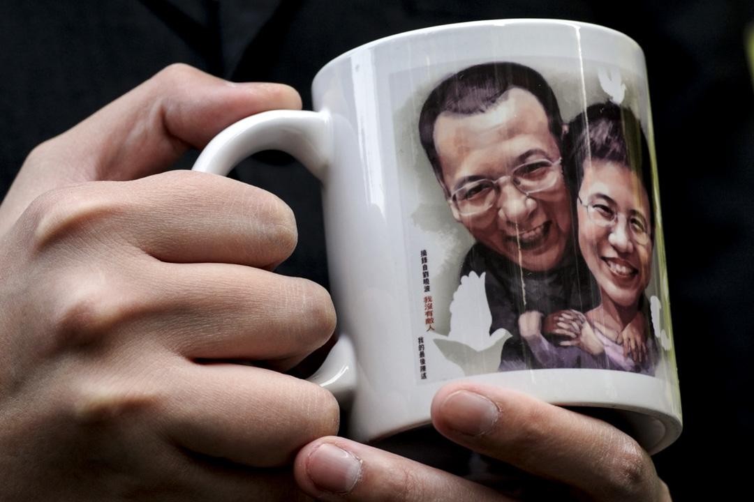 劉霞與劉曉波的肖象被印在示威者手持的杯上。