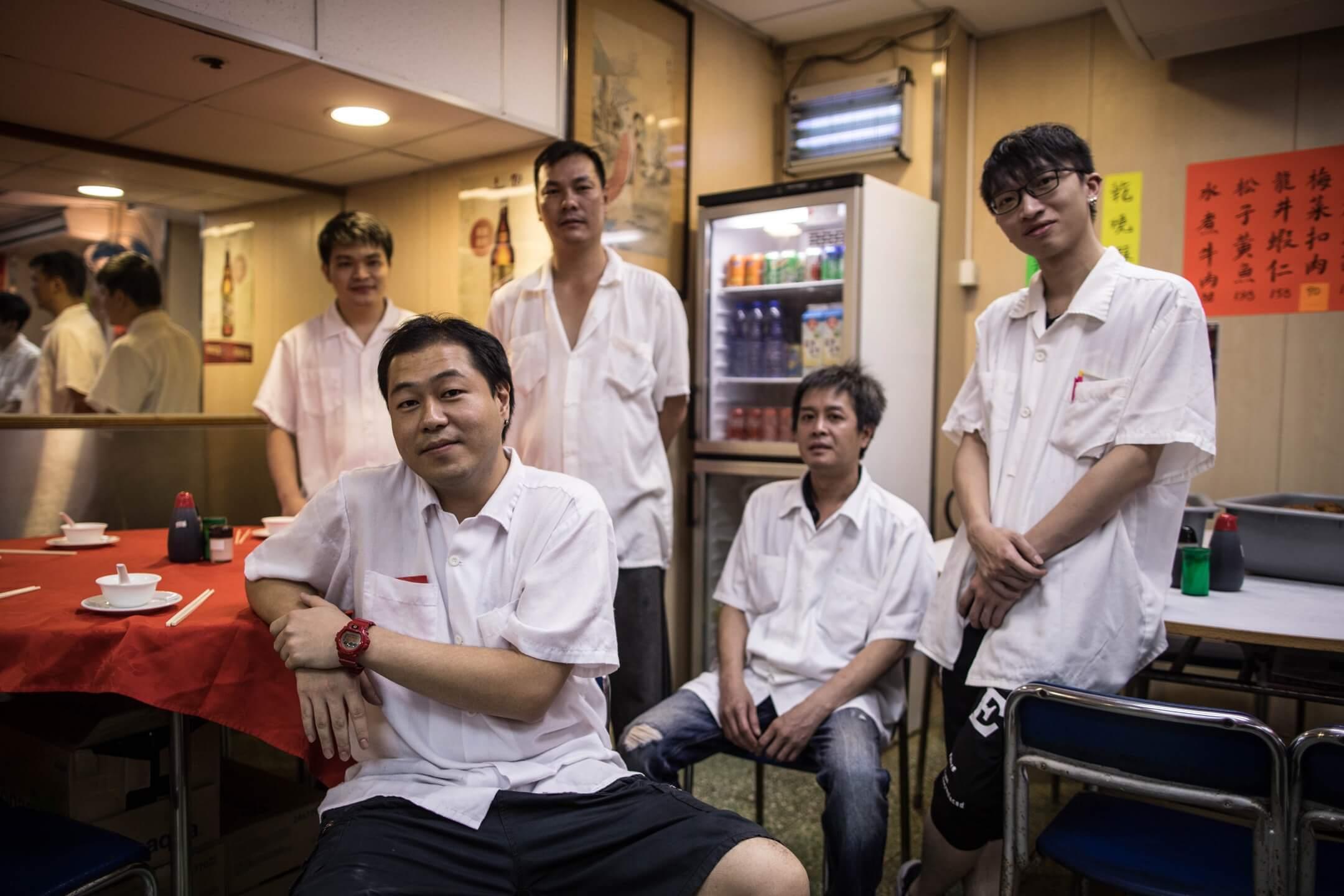 一位食客在食評網上寫道:「那種感覺就像走進80年代的飯館,場地直接可以用來拍老香港電影。」三六九餐廳老闆戴康富說,事實上,從搬過來就沒怎麼裝修過。客人都要求維持原樣。圖為老闆戴康富(前)與一眾餐廳伙記。 攝:Stanley Leung/端傳媒