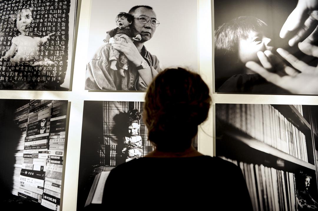 2011年10月19日,巴黎一個攝影展展出劉霞為劉曉波拍攝的肖像,相中劉曉波把一個醜娃娃抱在肩上。「醜陋的嬰兒」隱喻中國人民的身心痛苦、言論自由受箝制的壓抑與沉默。 攝:Mehdi Fedouach/AFP/Getty Images