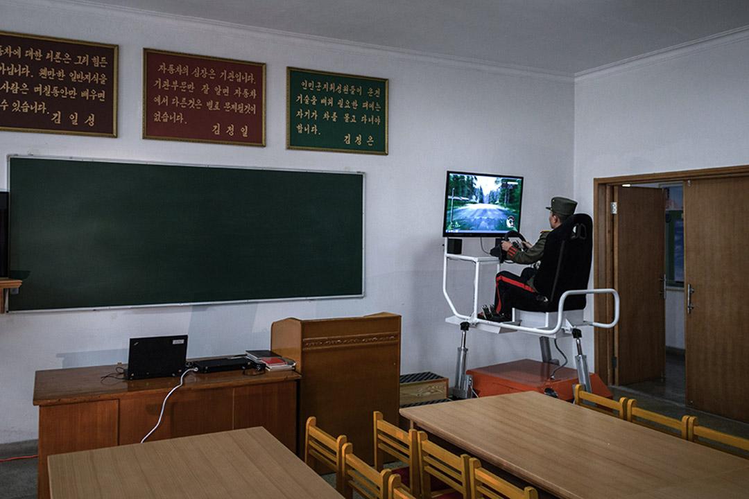 一名學生在萬景台革命學院的教室裡使用駕駛模擬器。