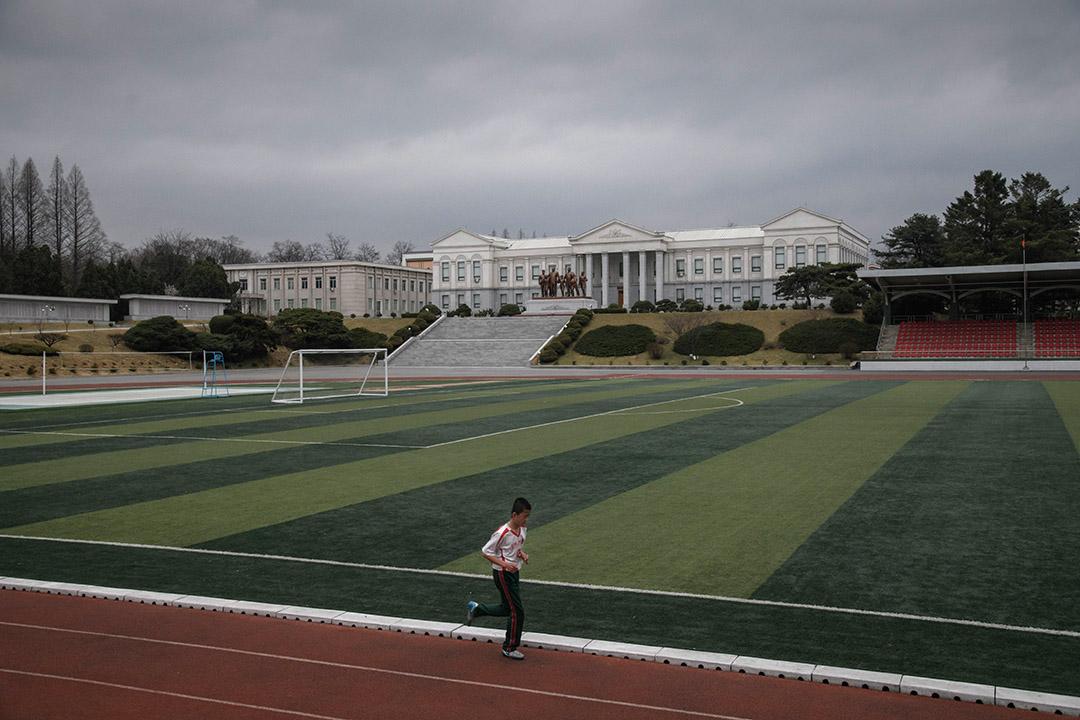 學生在萬景台革命學院的操場上跑步,背後豎立金日成和金正日父子與男學生並肩而行的銅像。