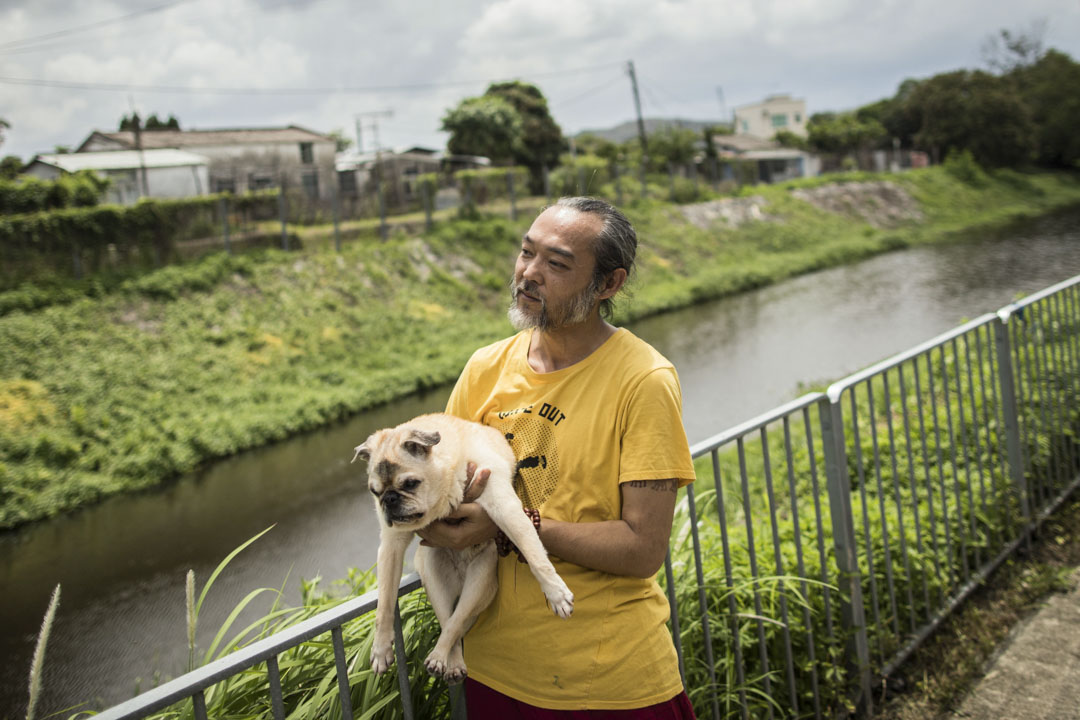午後的馬尾下村,平靜、安然,MC仁抱著八哥Gudii走過梧桐生態河。