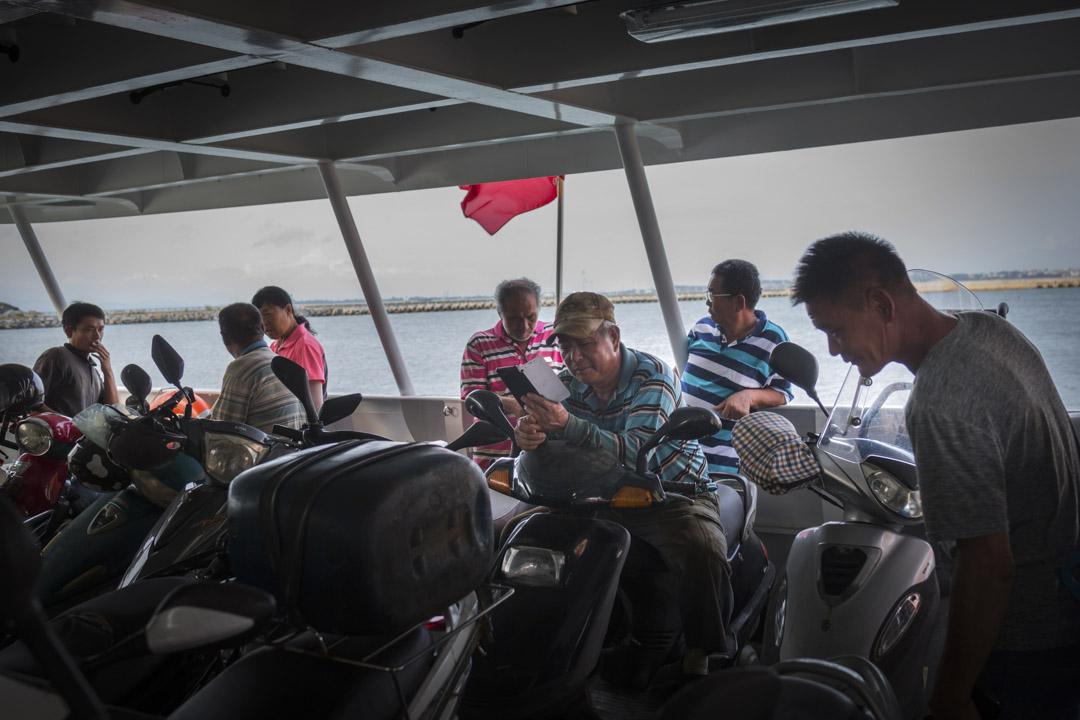 連接金門與小金門的渡輪上,騎電單車的居民正等候靠岸。
