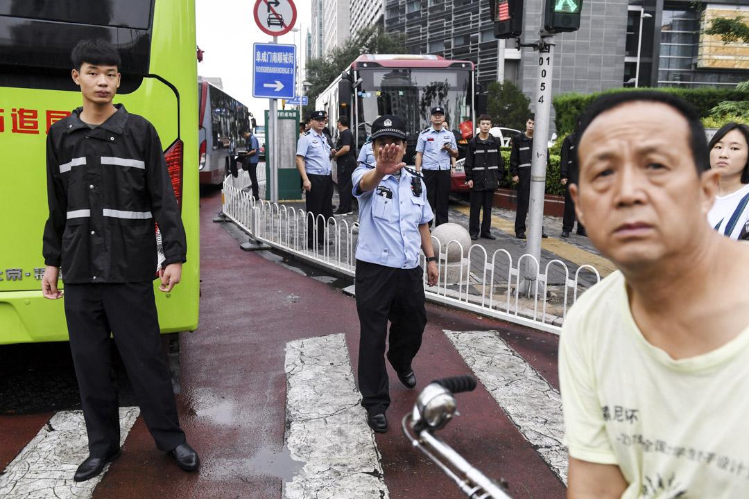 2018年8月6日,北京警方站在中國銀行業監管委員會面前維持秩序,以應對近日不少「P2P」上訪維權人士。 攝:Greg Baker/AFP/Getty Images