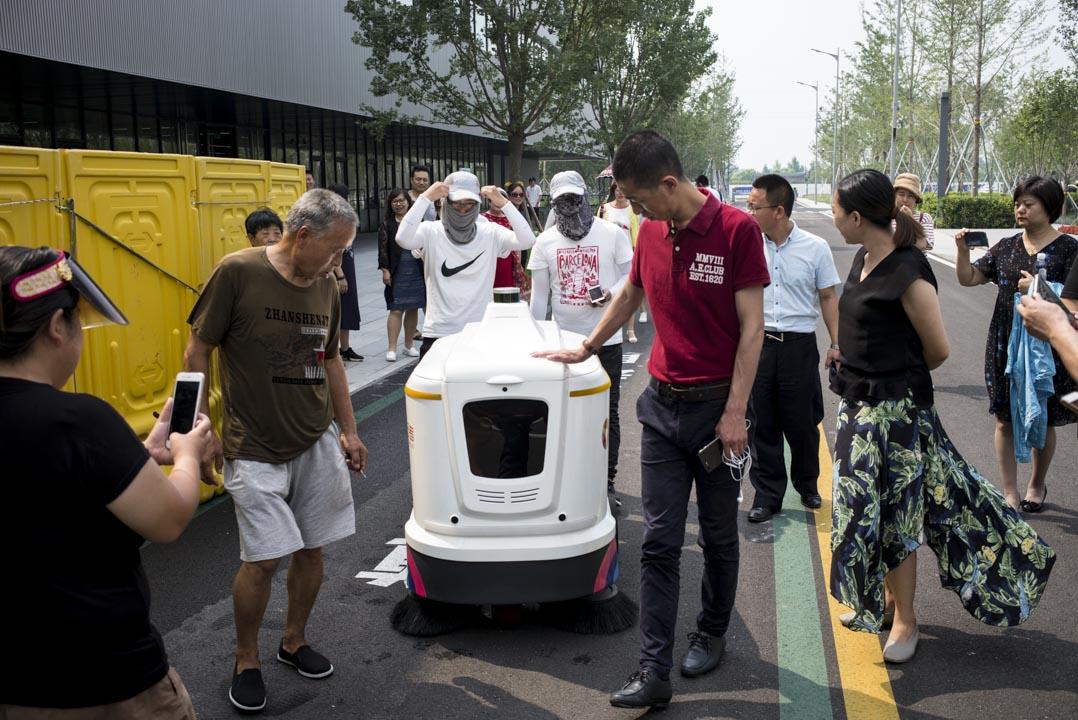 人群圍住了一輛正在運行的「無人駕駛掃路機」。